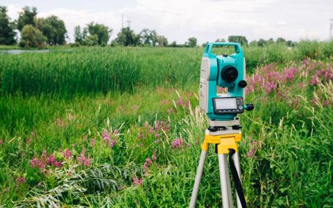 Surveying equipment on a field background